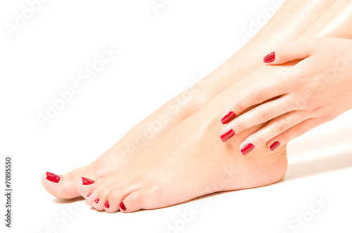 Beautiful female feet and hands with red nail polish