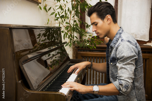 Fotografie, Obraz  Young handsome male artist playing his wooden classical upright