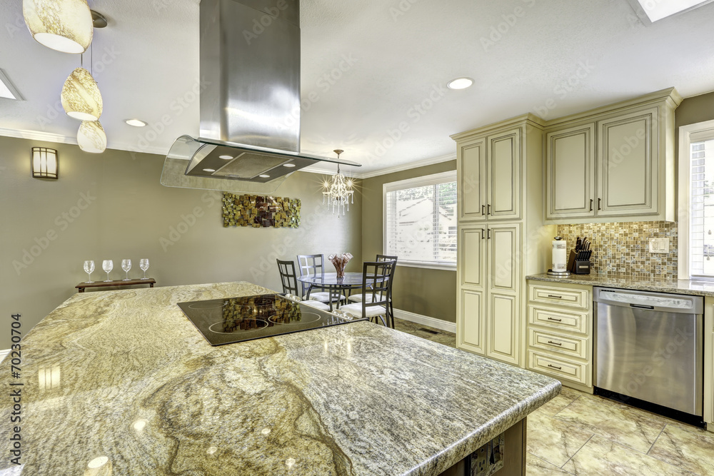 Fototapeta Beautiful kitchen island with granite top, built-in stove and ho