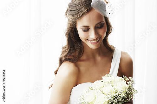 Fotografía  Young bride in wedding dress holding bouquet, studio shot .