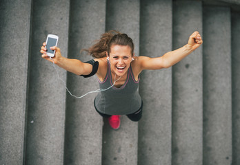 Fototapeta Portrait of happy fitness young woman with cell phone