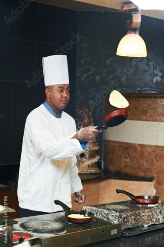 Spoed Foto op Canvas Pizzeria chef juggling with pancake on pan