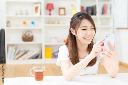 Photo 部屋でスマートフォンを見る女性