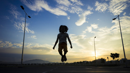 Silhouette girl jumping at open area with sunrise background
