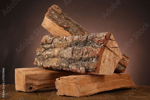 Fotomural Heap of firewood on floor on dark background
