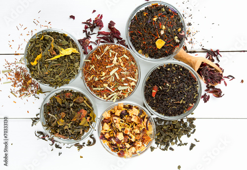Photo  assortment of dry tea in glass bowls on wooden surface