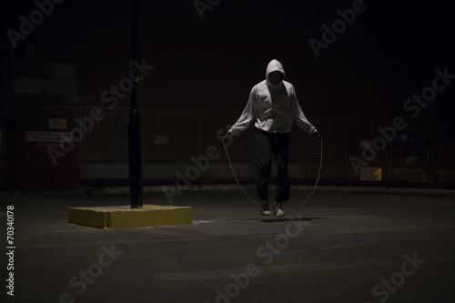 Fotografía  Atleta con capucha saltar por la noche bajo una farola