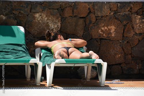 Poster de jardin Havana mujer tomando el sol a la orilla de una piscina