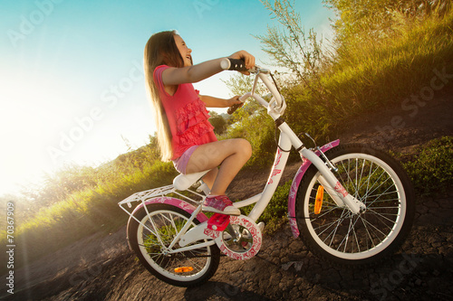 Poster Cycling Happy little girl riding a bicycle