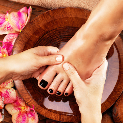 Massage of woman's foot in spa salon Poster