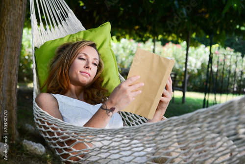Poster  cheerful young woman reading a book in a hammock