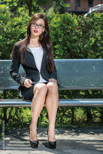 Photo  Beautiful businesswoman is sitting on the bench. Working with ta