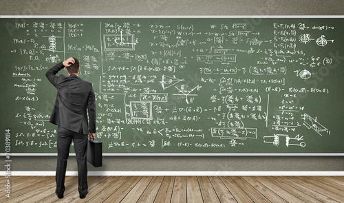 Foto Mann steht vor Wandtafel mit vielen Formeln