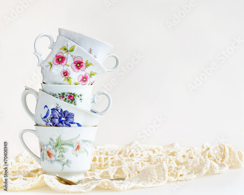 Stack of vintage tea cups on white