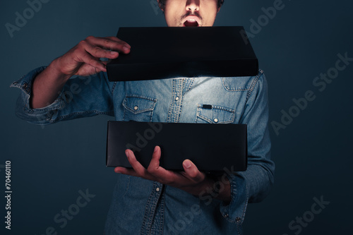 Valokuva  Young man opening an exciting box