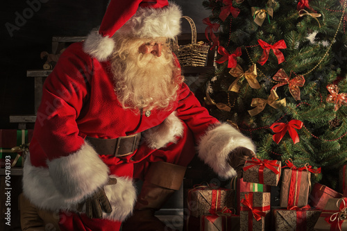 Fotografie, Tablou Santa is placing gift boxes under Christmas tree