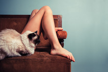 Young Woman With Cat Relaxing On Sofa