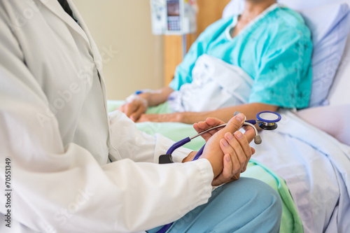 Fotografia  Female Doctor Sitting With Patient On Hospital Bed