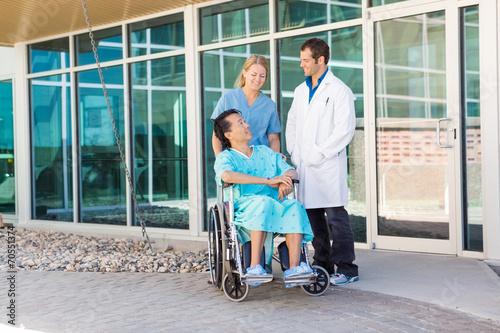 Foto  Krankenschwester And Doctor, die Patienten auf Rollstuhl außerhalb Hospit betrac