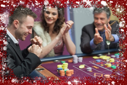 Photo  Composite image of people cheering man at craps game