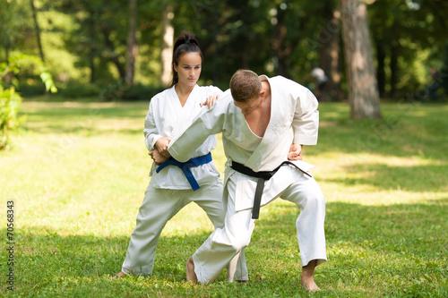 Staande foto Vechtsport Two martial arts fighters practicing in nature.