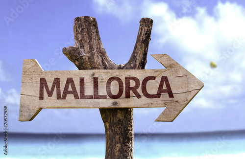 Photo Mallorca wooden sign with a beach on background