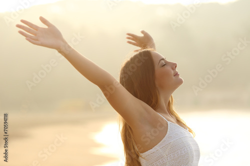Deurstickers Ontspanning Relaxed woman breathing fresh air raising arms at sunrise