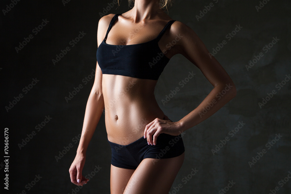 Fototapeta Slim woman's body  over dark grey background