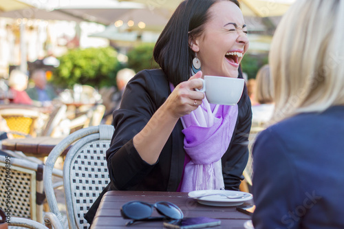 Young cheerful woman laughing while chatting with friend Fototapeta