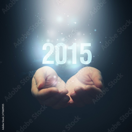 Fotografia  Open hands holding number 2015. Happy New Year.