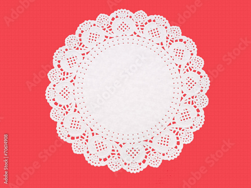 Valokuva  Fancy paper doily, round, perforated, embossed, on textured red.