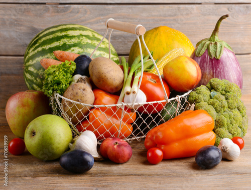 Fresh organic fruits and vegetables on wooden background © Africa Studio