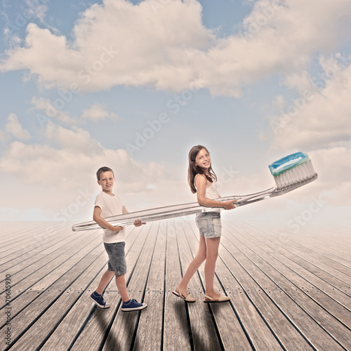 Plakat two children holding a big toothbrush on a wharf