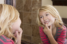 Child Looking In Mirror At Missing Front Tooth