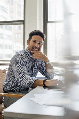 Office life. A man sitting at a desk looking at the camera.