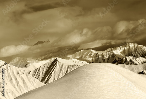 Sepia off-piste snowy slope and cloudy mountains