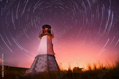 lighthouse with night sky at background stars trails Fototapeta