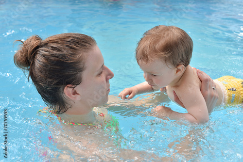 Fotografía  One year baby girl at his first swimming lesson with her mother