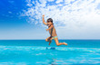 Boy jumps in swimming pool with seaside background