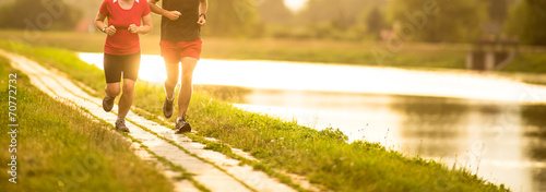 Foto Couple running outdoors, at sunset, by a river