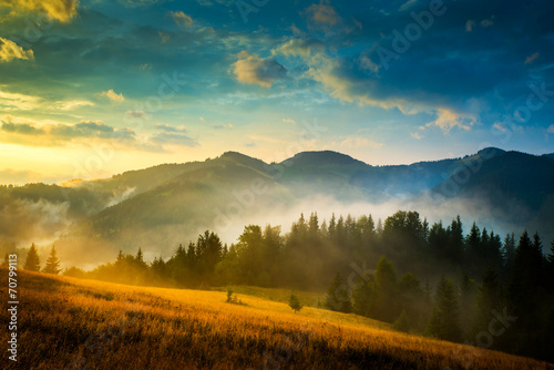 Poster de jardin Bleu nuit Amazing mountain landscape with fog and a haystack