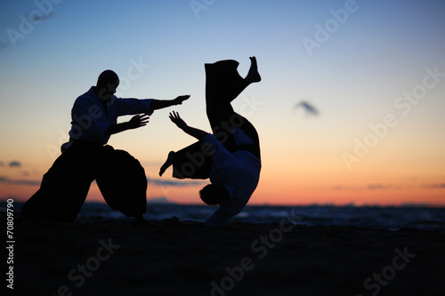 Photo Practicing aikido technique, silhouettes of masters