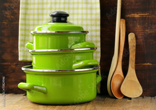 Fotomural set of metal green pots cookware on a wooden background