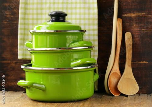 Fotografía set of metal green pots cookware on a wooden background