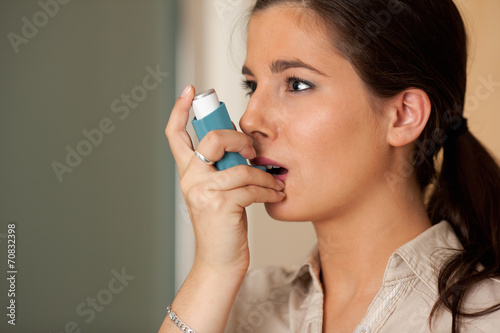 Obraz na plátně Woman using asthma inhaler