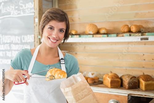 Foto op Plexiglas Bakkerij Pretty waitress picking up croissant