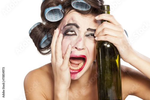 Tela young drunk woman with curlers crying next to a bottle of wine