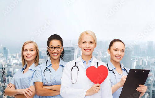 Fotografia  smiling female doctor and nurses with red heart