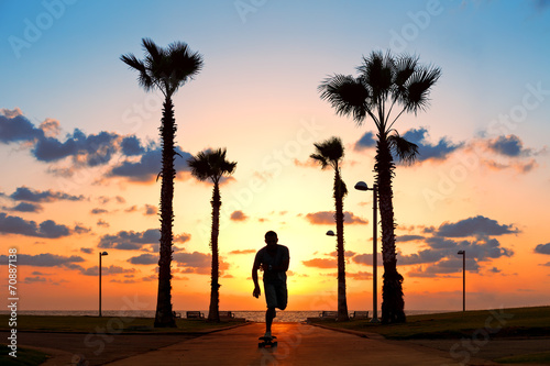 man riding on skateboard near the ocean in sunset