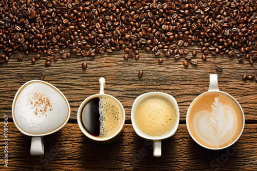Variety of cups of coffee and coffee beans on old wooden table #70894369